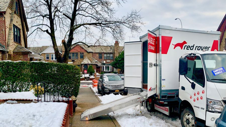 red rover truck with ramp deployed on snowy street
