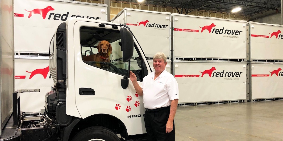 peter warhurst with dog hunter sitting in red rover truck