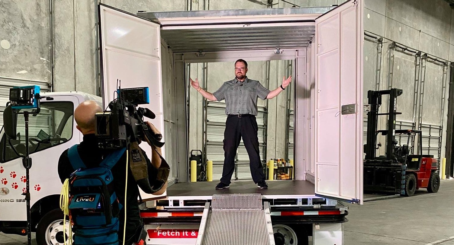 news reporter standing inside red rover container